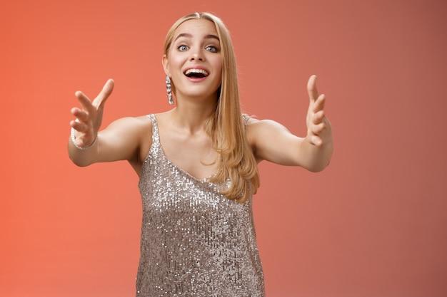 Podekscytowany czarownik dotknął rozgrzewającej młodej blond kobiety w srebrnej sukience glamour wyciągnąć ręce w kierunku aparatu rozbawiony chce przytulić przytulić ramiona słodkiego szczeniaka, stojącego na czerwonym tle.
