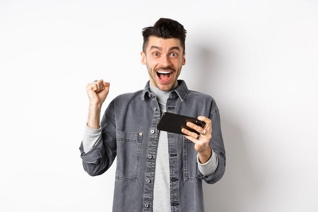 Podekscytowany człowiek zarabia pieniądze na telefonie komórkowym i raduje się, podnosząc rękę i krzycząc ze szczęścia i radości, stojąc ze smartfonem na białym tle.