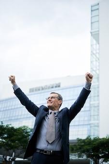 Podekscytowany dojrzały biznesmen rasy kaukaskiej w okularach i garniturze, chodzący z uniesionymi ramionami, świętujący sukces na świeżym powietrzu