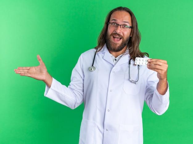 Podekscytowany dorosły mężczyzna lekarz ubrany w szatę medyczną i stetoskop w okularach, patrząc na kamerę pokazującą paczkę tabletek i pustą rękę na zielonej ścianie