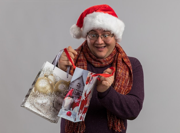 Podekscytowany dorosły mężczyzna w okularach i santa hat z szalikiem na szyi trzymający torby z prezentami świątecznymi, otwierający jeden patrzący do środka na białym tle na białej ścianie