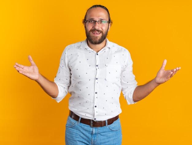 Podekscytowany dorosły przystojny mężczyzna w okularach pokazujący puste ręce patrzący na kamerę odizolowaną na pomarańczowej ścianie