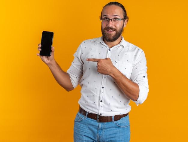 Podekscytowany dorosły przystojny mężczyzna w okularach pokazujący telefon komórkowy wskazujący na niego, patrzący na kamerę odizolowaną na pomarańczowej ścianie
