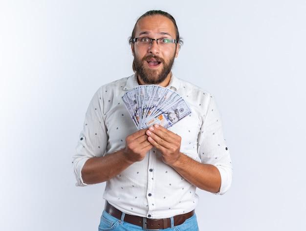 Podekscytowany dorosły przystojny mężczyzna w okularach trzymający pieniądze, patrzący na kamerę odizolowaną na białej ścianie