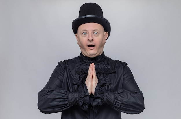 Podekscytowany dorosły słowiański mężczyzna w cylindrze i czarnej gotyckiej koszuli trzymający ręce razem i