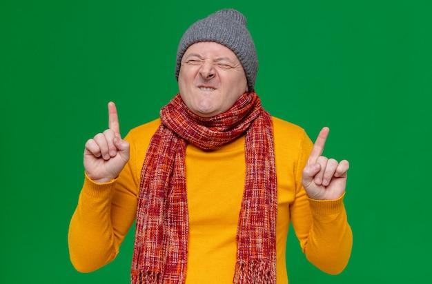 Podekscytowany dorosły słowiański mężczyzna w czapce zimowej i szaliku na szyi skierowanym do góry