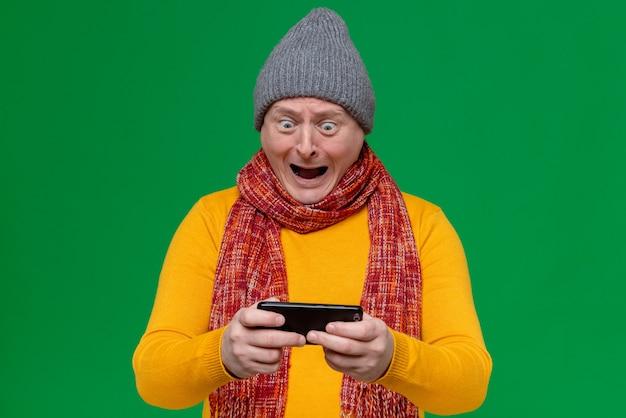 Podekscytowany dorosły słowiański mężczyzna w czapce zimowej i szaliku na szyi, trzymający i patrzący na telefon