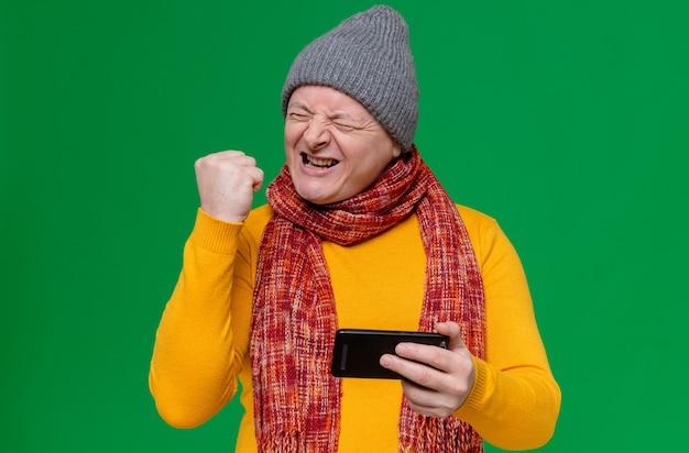 Podekscytowany dorosły słowiański mężczyzna w czapce zimowej i szaliku na szyi, trzymający telefon i trzymający pięść w górze