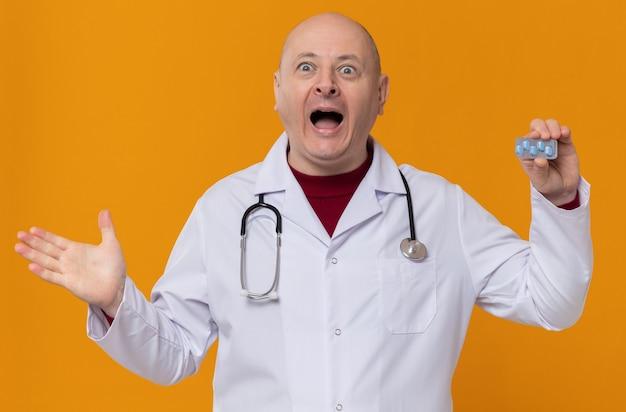 Podekscytowany dorosły słowiański mężczyzna w mundurze lekarza ze stetoskopem, trzymający blister z lekiem i trzymający otwartą dłoń