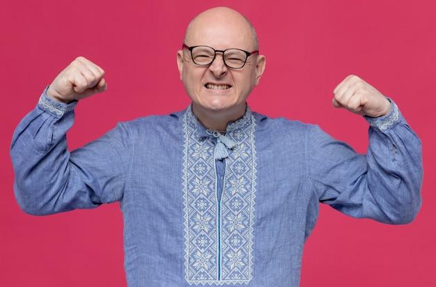 Podekscytowany dorosły słowiański mężczyzna w niebieskiej koszuli w okularach optycznych napinający biceps