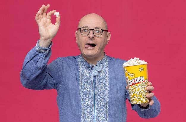 Podekscytowany dorosły słowiański mężczyzna w niebieskiej koszuli w okularach optycznych trzymający wiadro popcornu