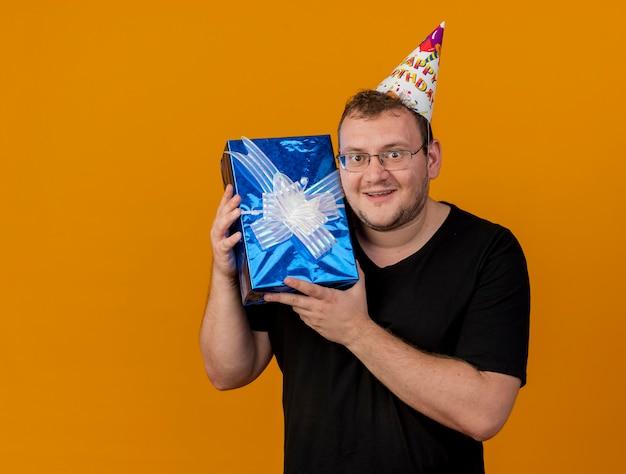Podekscytowany dorosły słowiański mężczyzna w okularach optycznych w czapce urodzinowej trzyma pudełko upominkowe