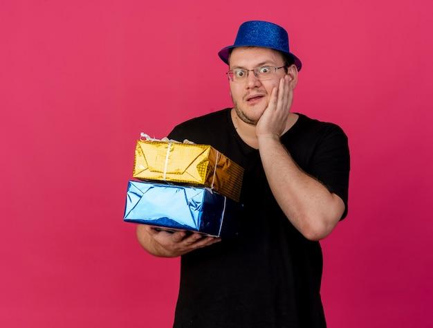Podekscytowany dorosły słowiański mężczyzna w okularach optycznych w niebieskiej imprezowej czapce kładzie rękę na twarzy i trzyma pudełka na prezenty