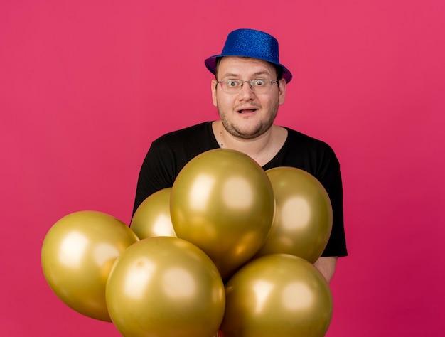 Podekscytowany dorosły słowiański mężczyzna w okularach optycznych w niebieskiej imprezowej czapce trzyma balony z helem