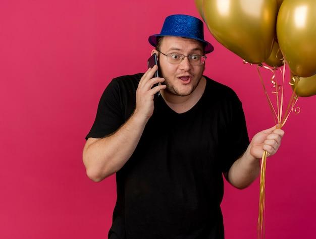 Podekscytowany dorosły słowiański mężczyzna w okularach optycznych w niebieskim kapeluszu imprezowym trzyma balony z helem rozmawia przez telefon