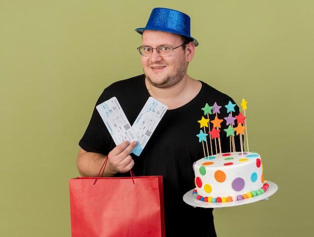 Podekscytowany dorosły słowiański mężczyzna w okularach optycznych w niebieskim kapeluszu imprezowym trzyma papierową torbę na zakupy tort urodzinowy i bilety lotnicze