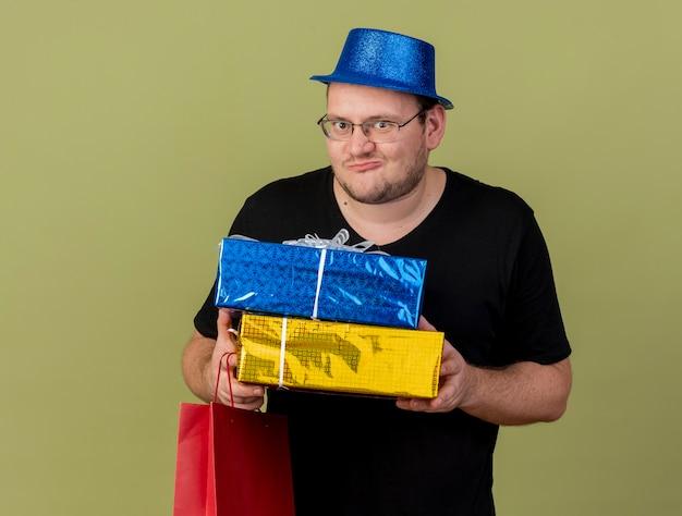 Podekscytowany dorosły słowiański mężczyzna w okularach optycznych w niebieskim kapeluszu imprezowym, trzyma pudełka na prezenty i papierową torbę na zakupy