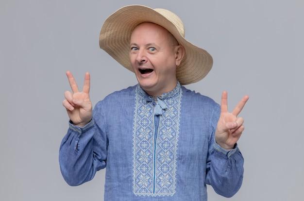 Podekscytowany dorosły słowiański mężczyzna w słomkowym kapeluszu i niebieskiej koszuli gestykulujący znak zwycięstwa