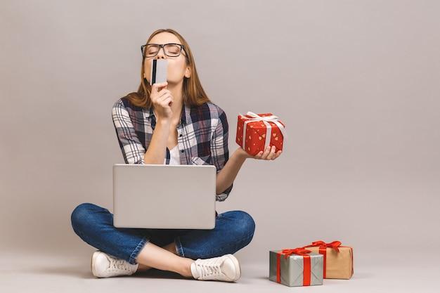Podekscytowany dorywczo dziewczyna trzyma laptop i kartę kredytową, siedząc na podłodze ze stosem pudełek