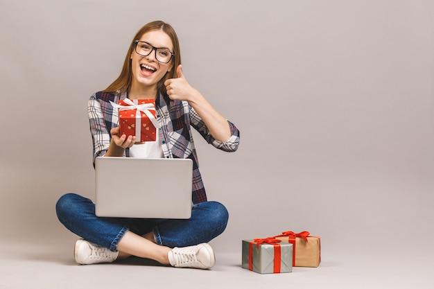 Podekscytowany dorywczo dziewczyna trzyma laptopa siedząc na podłodze ze stosem pudełek. kciuki w górę.