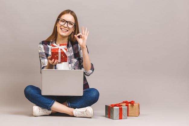 Podekscytowany dorywczo dziewczyna trzyma laptopa siedząc na podłodze ze stosem pudełek
