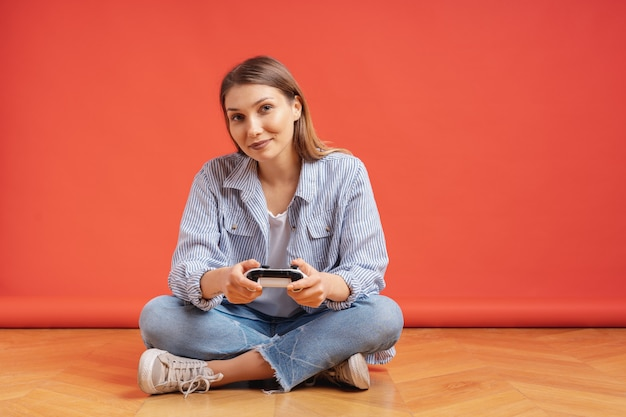 Podekscytowany dorywczo młoda kobieta grając w gry wideo zabawy na czerwono