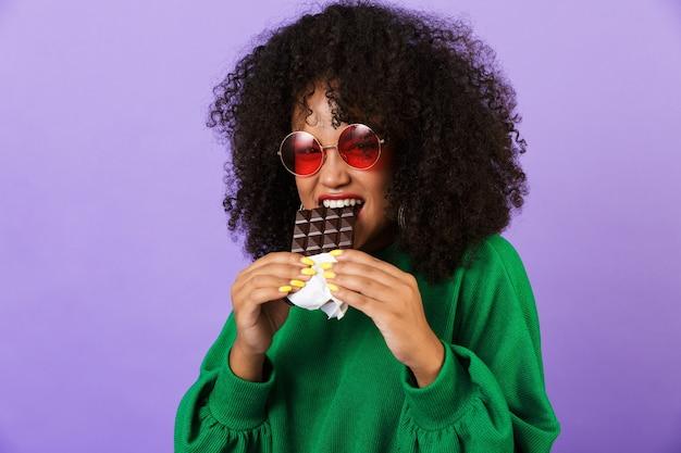Podekscytowany dość afrykańska kobieta na białym tle nad fioletową przestrzeń jeść czekoladę.