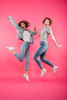 Podekscytowany dwóch przyjaciół pań skoki na białym tle