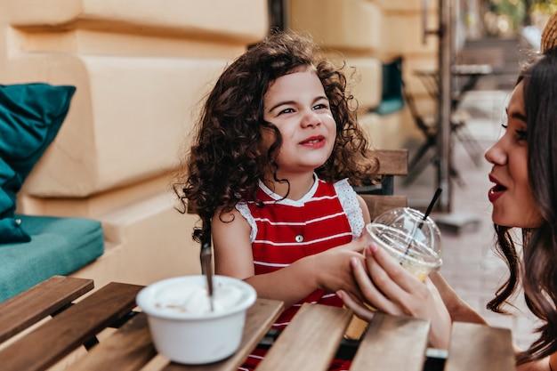 Podekscytowany dzieciak je lunch w kawiarni. pozytywna mała dziewczynka siedzi w ulicznej restauracji z matką.