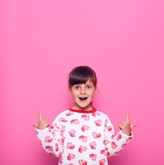 Podekscytowany dziecko płci żeńskiej z otwartymi ustami, patrząc bezpośrednio na aparat z wyrazem zdumienia, wskazując palcem wskazującym w górę, kopiuj przestrzeń, odizolowane na różowej ścianie.