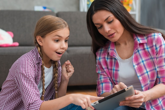 Podekscytowany dziewczyna palcem wskazującym na cyfrowe tabletki wyświetlane przez kobiece psychologa