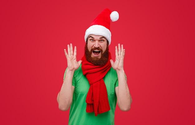 Podekscytowany elf świętego mikołaja w czapce i szaliku, gestykulujący i wrzeszczący
