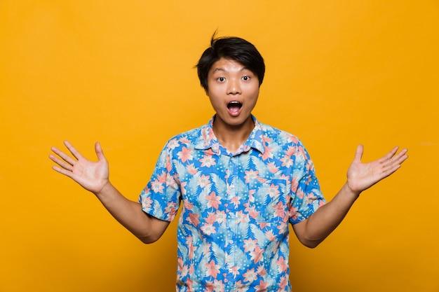 Podekscytowany emocjonalny młody człowiek azjatycki pozowanie na białym tle nad żółtą przestrzenią.