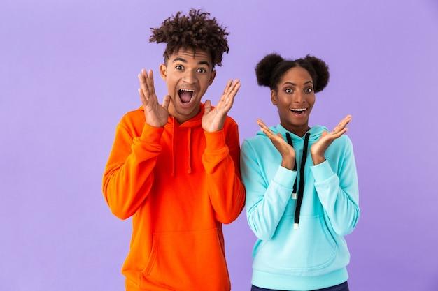 Podekscytowany facet i dziewczyna stojąc razem i zabawy, odizolowane na fioletowej ścianie