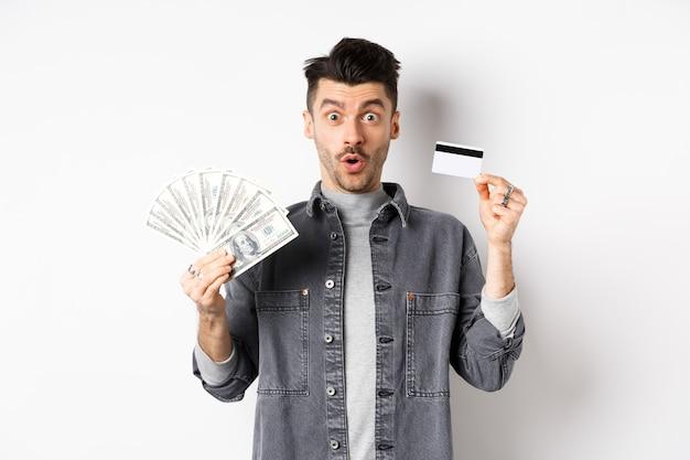 Podekscytowany facet trzyma plastikową kartę kredytową i dolary, stojący rozbawiony na białym tle.