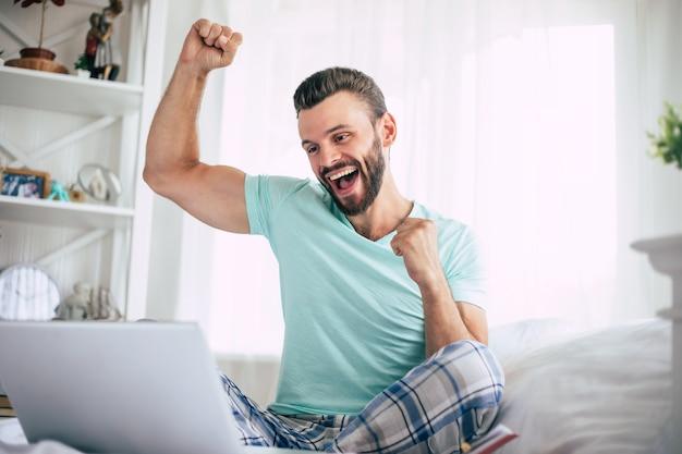 Podekscytowany fan szczęśliwej wygranej brodaty mężczyzna z laptopem w dużym białym łóżku w domu krzyczy podczas uroczystości