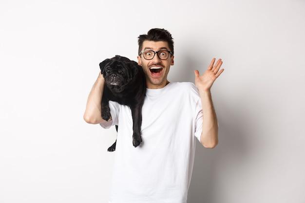 Podekscytowany hipster facet w okularach trzymający psa na ramieniu, machający ręką, by się przywitać, witający kogoś z uśmiechniętą twarzą. szczęśliwy człowiek nosi swojego słodkiego mopsa i uśmiechnięte, białe tło
