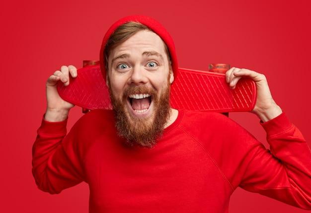 Podekscytowany hipster z czerwoną deskorolką