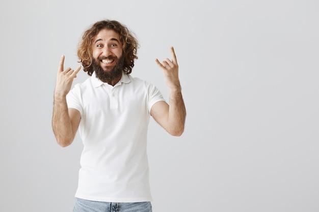 Podekscytowany i szczęśliwy człowiek z bliskiego wschodu pokazujący rock-n-rollowy gest, bawiący się
