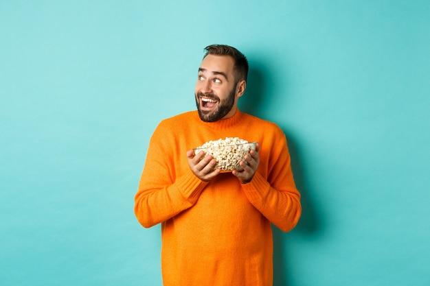 Podekscytowany i szczęśliwy mężczyzna ogląda telewizję i trzyma miskę popcornu, patrząc w lewo i uśmiechnięty zadowolony, stojąc na niebieskim tle.
