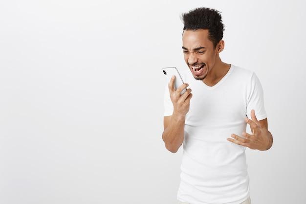 Podekscytowany i szczęśliwy triumfujący afroamerykanin patrząc na ekran telefonu komórkowego z podekscytowaną twarzą, radując się