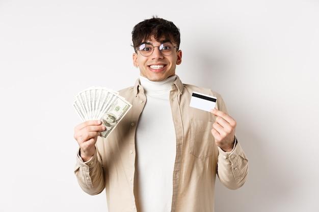 Podekscytowany i szczęśliwy uśmiechnięty mężczyzna trzyma pieniądze i plastikową kartę kredytową, stojąc na białej ścianie.