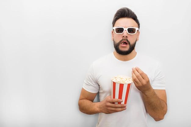 Podekscytowany i zdumiony młody człowiek stoi i oczekuje. nosi okulary filmowe. facet trzyma wiadro popcornu. jego usta są otwarte.