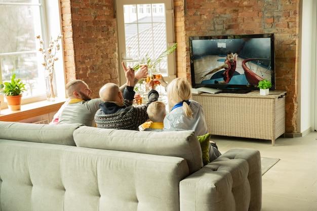 Podekscytowany kaukaski rodzina ogląda mistrzostwa koszykówki, mecz sportowy w domu. dziadkowie, rodzice i dzieciak dopingują ulubioną drużynę narodową. pojęcie ludzkich emocji, wsparcia, wspólnoty.