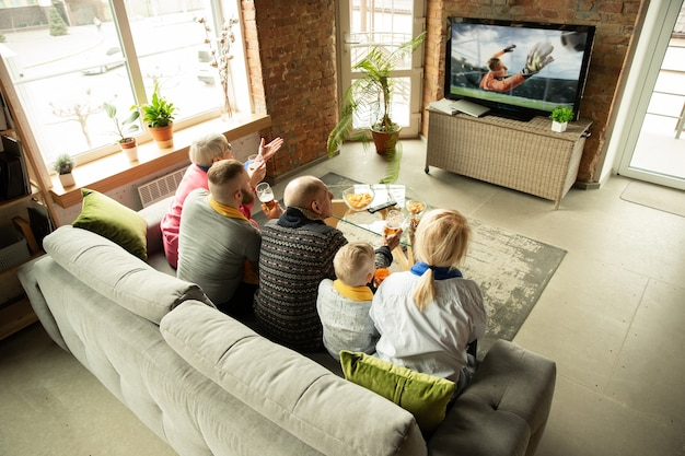 Podekscytowany kaukaski rodziny oglądanie piłki nożnej, mecz piłki nożnej w domu. dziadkowie, rodzice i dzieciak dopingują ulubioną drużynę narodową. pojęcie ludzkich emocji, wsparcia, wspólnoty.