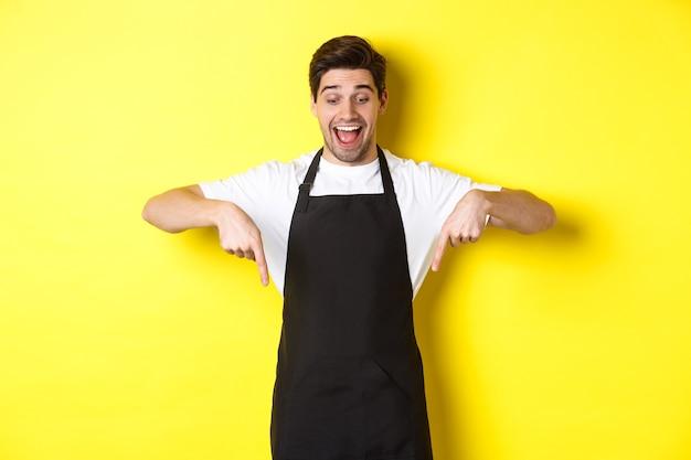 Podekscytowany kelner w czarnym fartuchu, wskazujący palcami w dół, sprawdzający ofertę promocyjną, stojący na żółtym tle.