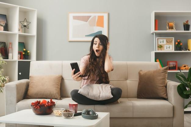 Podekscytowany, kładąc dłoń na głowie, młoda dziewczyna trzyma i patrzy na telefon, siedząc na kanapie za stolikiem kawowym w salonie