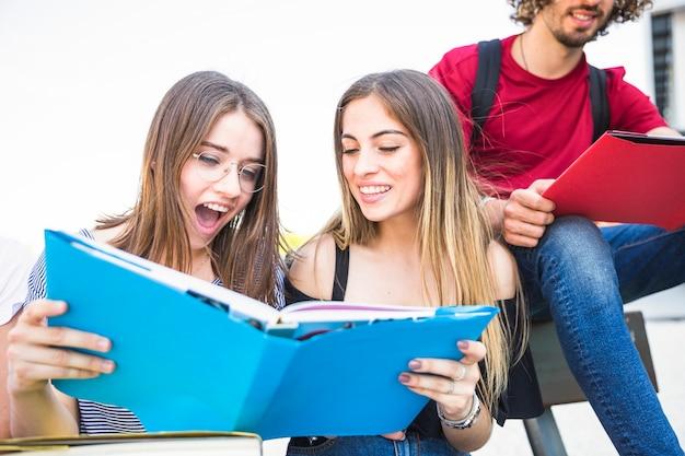 Podekscytowany kobiet czytania podręcznika w pobliżu człowieka