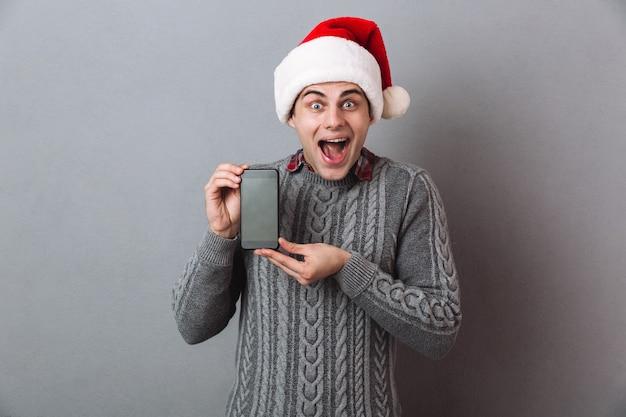 Podekscytowany krzyczący emocjonalny mężczyzna ubrany w świąteczny santa hat