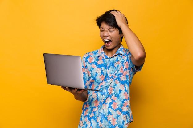 Podekscytowany krzyczący zszokowany młody azjatycki mężczyzna stojący na białym tle nad żółtą przestrzenią za pomocą laptopa.